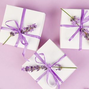 White Gift box with violet ribbon and bouquet of flower lavender on pink background. Celebration, birthday. Decoration present. Flat lay. Copy space.
